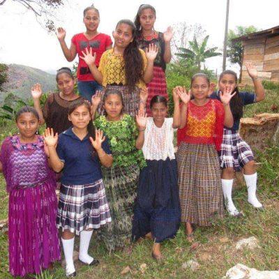 Flickor från Guatemala vinkar till kameran, plan international